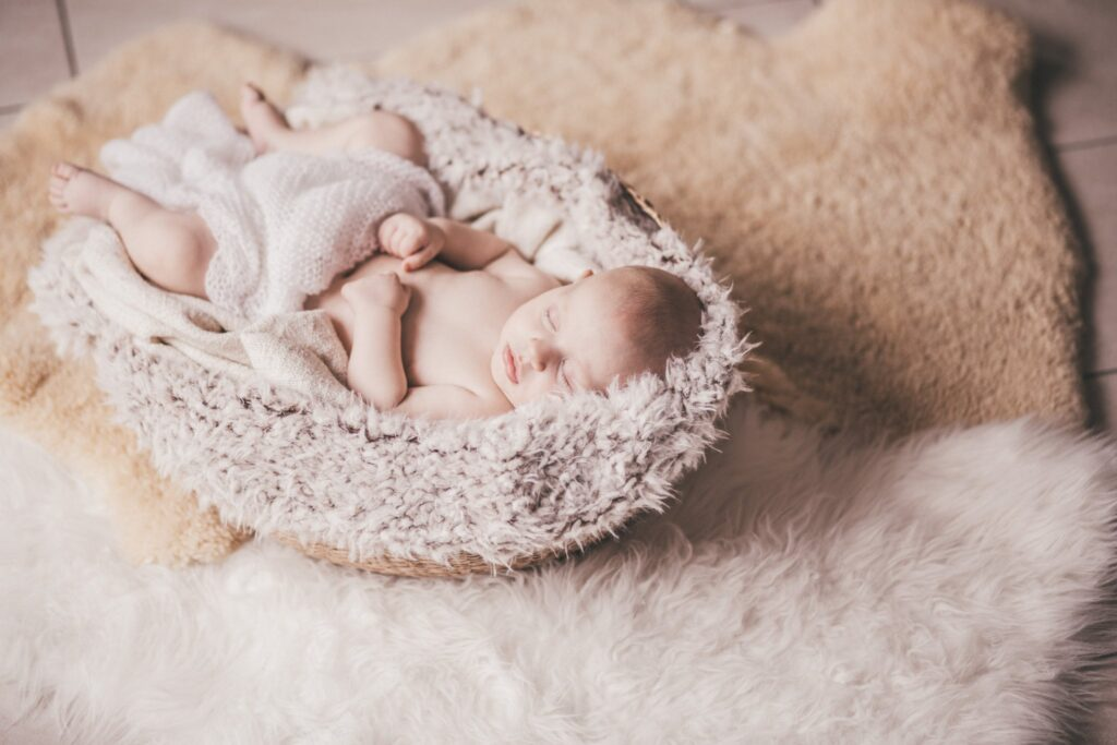 Neugeborenes im Körbchen mit Decke beim Fotoshooting