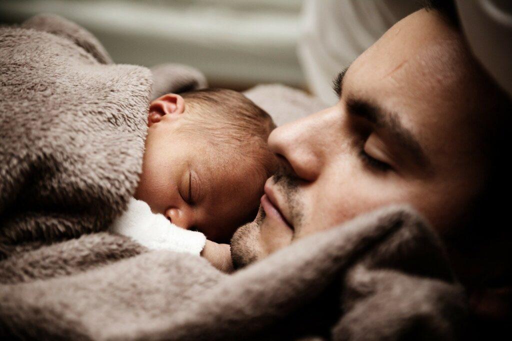 Schlafendes Baby auf der Brust des schlafenden Vaters